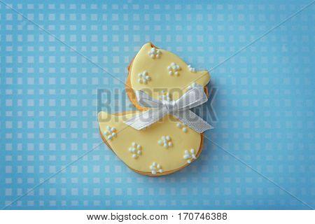 Baby cookie decorated with glaze on color background