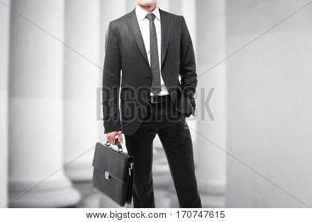 Law and justice concept. Man with briefcase on courthouse background
