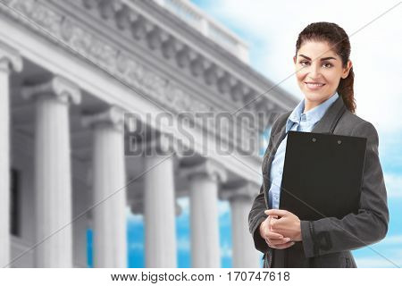 Law and justice concept. Mature woman with clipboard on courthouse background