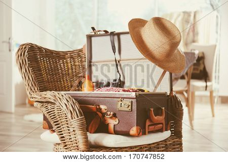Packed suitcase on wicker chair at home. Travel and vacation concept