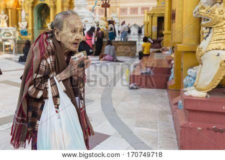 RANGOON, MYANMAR - JANUARY 18, 2017 : An elderly woman is praying Buddha at the Shwedagon pagoda in Rangoon (Yangon), Myanmar