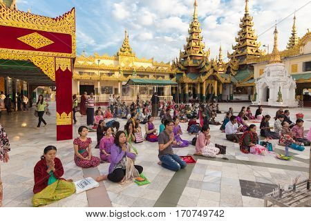 RANGOON, MYANMAR - JANUARY 18, 2017 : Burmese people sitting and praying Buddha at the Shwedagon pagoda in Rangoon (Yangon), Myanmar