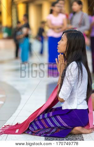 RANGOON, MYANMAR - JANUARY 18, 2017 : A woman is praying at the Shwedagon pagoda in Rangoon (Yangon), Myanmar