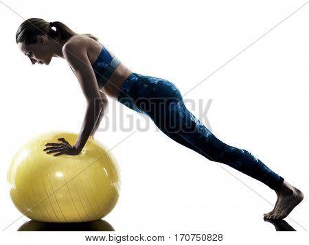 one caucasian woman exercising fitness swiss ball excercises in silhouette isolated on white background