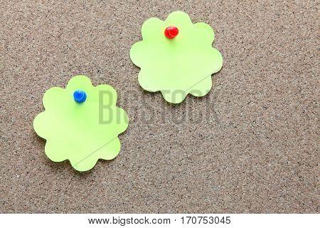 two flower shape memo paper on cork board