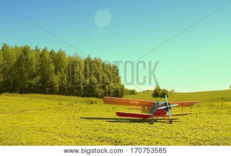 Biplane pure deserted field. Watering aircraft without a pilot in the meadow