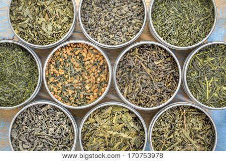 green tea sampler - top view of loose leaves  in metal cans against grunge wood