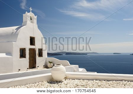 White orthodox church with bell tower. Oia, Santorini Greece. Copyspace