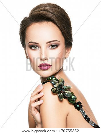 Beautiful woman with fashionable jewelry.  Portrait of a pretty fashion girl with green glass necklace. American Model posing over white background