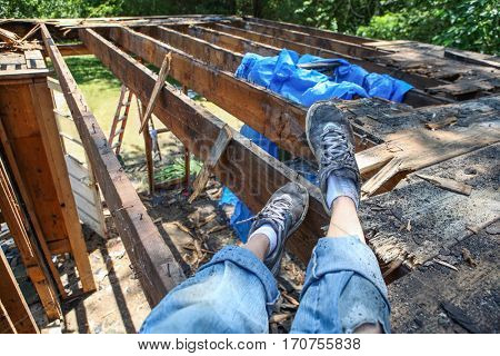 Person resting while tearing down an addition on a house