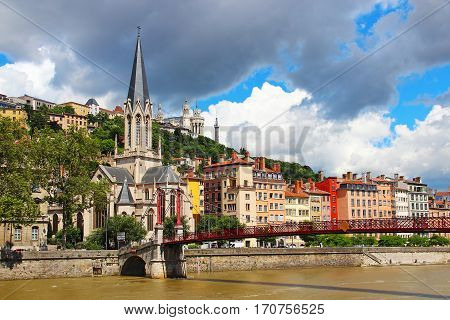 St. Georges church and St. Georges bridge over Saone river with Basilica of Notre-Dame de Fourviere on the background, Lyon, France