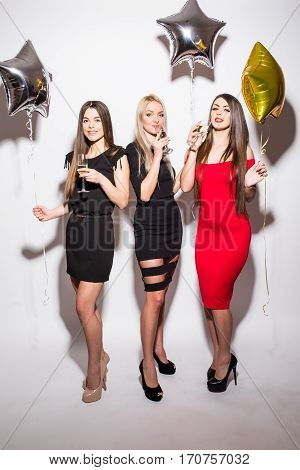 Cheerful young women drinking champagne talking and laughing with balloons on the party over white background