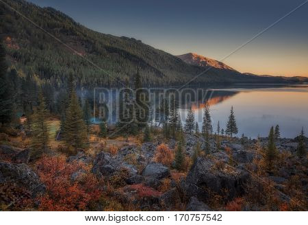 Sunset Lake View With Calm Water And Evergreen Forest On The Shore, Altai Mountains Highland Nature Autumn Landscape Photo. Beautiful Russian Wilderness Scenery Image.