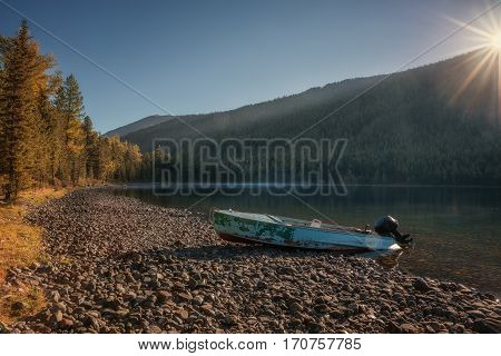 River With Thick Forest And Abandoned Speedboat On The Bank, Altai Mountains Highland Nature Autumn Landscape Photo. Beautiful Russian Wilderness Scenery Image.