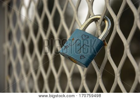 Detail of padlock locked on mesh. Heart and J+F wroten on padlock