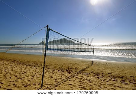 Beach volleyball in the sand of Mazatlan, Mexico with the island in the background