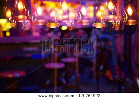 blur purple light on bar or pub background with lamp at night