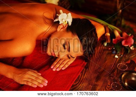 Massage of woman in spa salon. Girl on candles background in massage spa salon. Luxary interior in oriental therapy salon. Top view of female have relax after sports training.