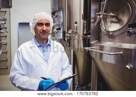 Portrait of confident manufacturer with writing pad standing amidst storage tanks at brewery