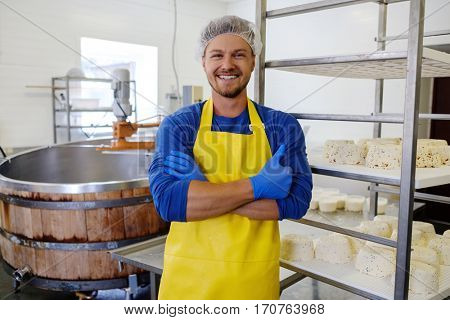 Handsome cheesemaker making curd cheese in his factory