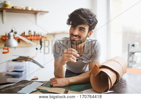 Portrait of handsome middle eastern man wearing creative haircut looking away and smiling, leaning on workshop table while creating leather designs in studio