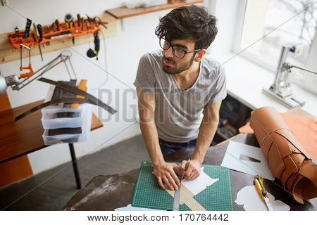 High angle portrait of muscular middle eastern man wearing creative haircut and glasses looking away thoughtfully, while creating leather designs in workshop studio