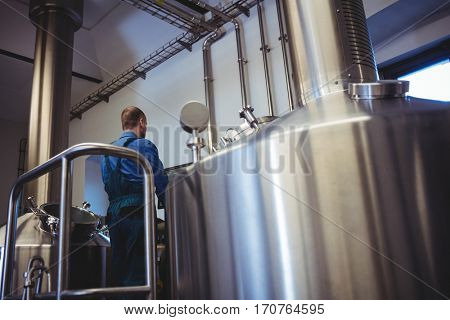 Rear view of manufacturer working at brewery