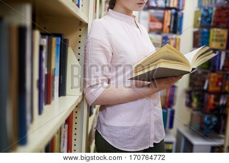 Adolescent student reading book in library or choosing book in book-shop