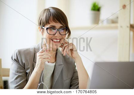 Portrait of young successful businesswoman holding videochat using hands free mic and laptop at workplace in modern office against window
