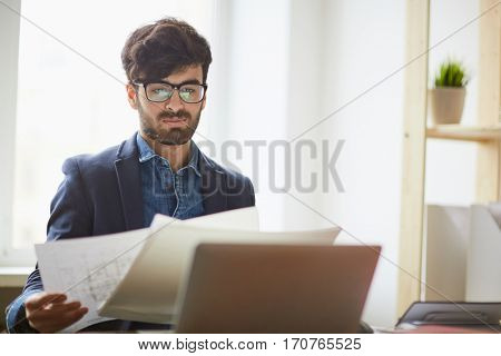 Young successful creative designer at workplace: middle eastern man sitting against window looking at construction plans and building documentation in light office