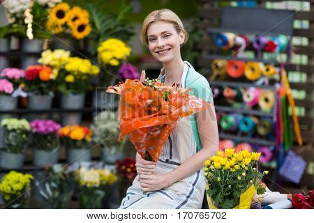 Portrait of happy female florist holding flower bouquet in the shop