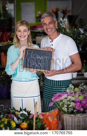 Portrait of smiling florists holding flower shop sign on slate in flower shop