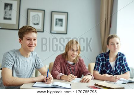 Group of teens listening to their teacher at lesson