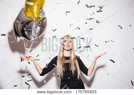 Blonde woman in black dress holding star balloon with fly confetti at party over white background