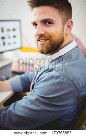 Portrait of confident happy young male editor working at creative office