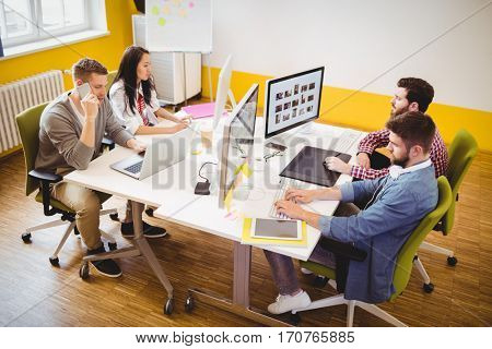 High angle view of young photo editors working at creative office
