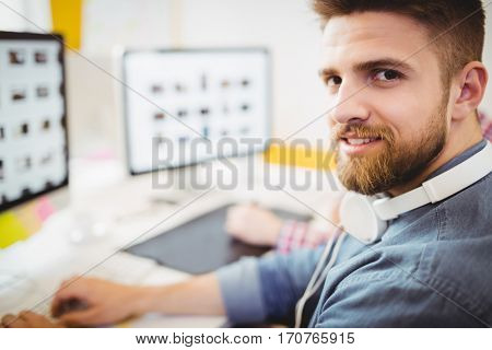 Portrait of confident young male photo editor working at creative office