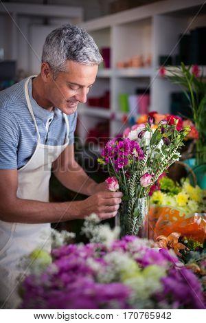 Smiling florist preparing a flower bouquet in flower shop