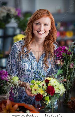 Portrait of female florist checking a flowers arrangement in vase at flower shop