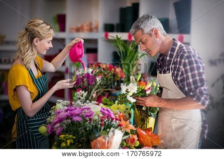 Female florist watering flowers with watering can in flower shop