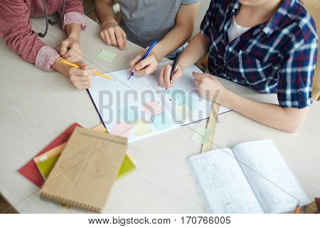 Over-view of group of students working by desk