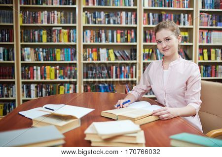 Happy girl looking at camera while working in library