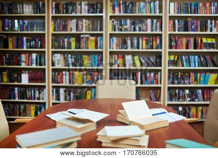 Empty library with bookshelves, desk, some open books and copybooks
