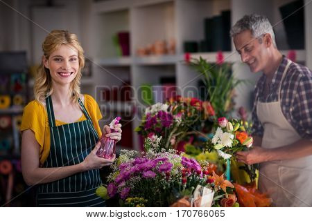 Portrait of smiling florist spraying water on flowers in flower shop