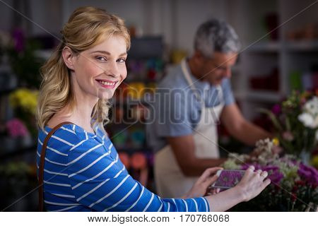 Portrait of smiling woman taking photograph of flower bouquet in flower shop