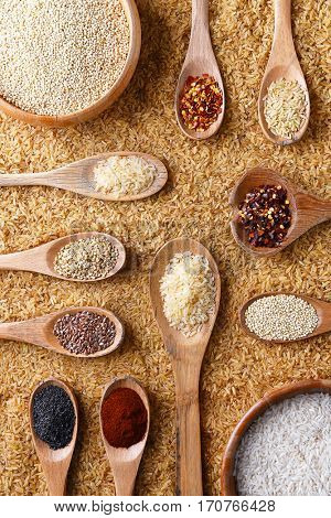Top view of a bed of brown rice with bowls and spoons with various rices, grains and spices.