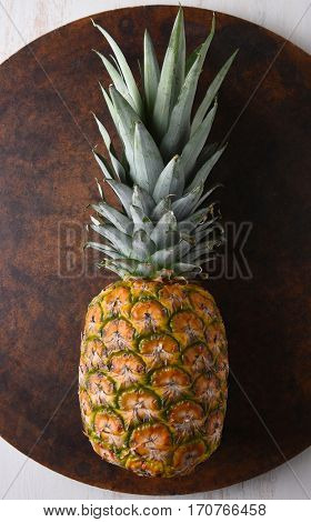 Top view of a fresh ripe pineapple on a round stone surface.
