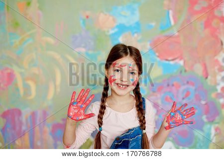 Cute girl with painted palms standing against creative wall