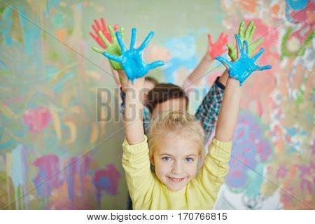 Cheerful kids raising their painted palms