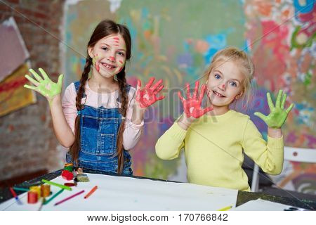 Two funny girls with green and red paint on palms